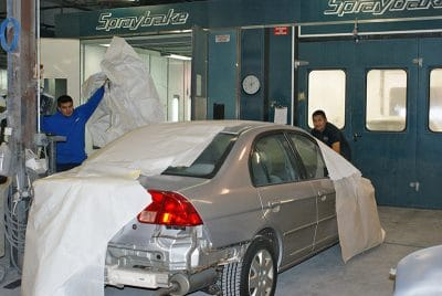 Picture of a silver car in a paint booth being repaired