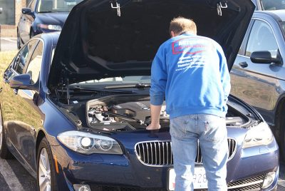 Picture of technician inspecting the engine compartment of a blue BMW